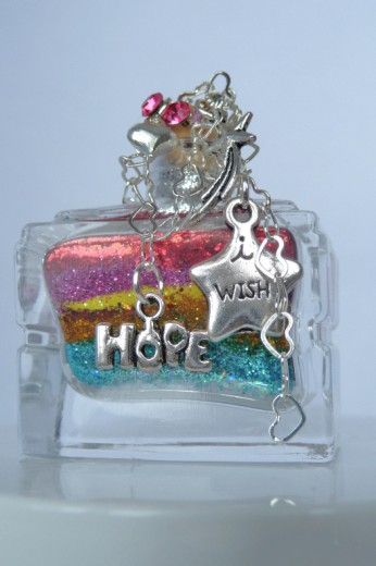 uniquely decorated mini bottle filled with colorful layers and adorned with hope and wish charms