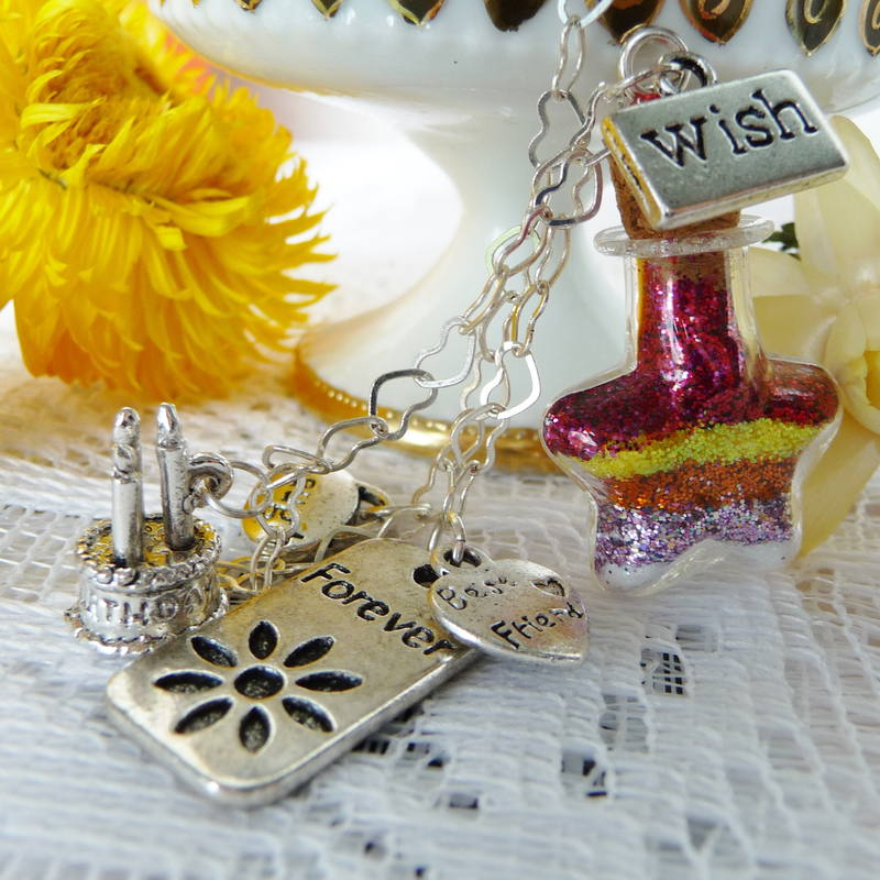 Closeup Of Birthday And Bff Charms Attached To Tiny Wish Vessel With Colorful Layers