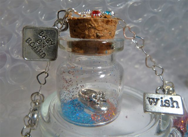 Close-up of a wish bottle holding mini baby shoe