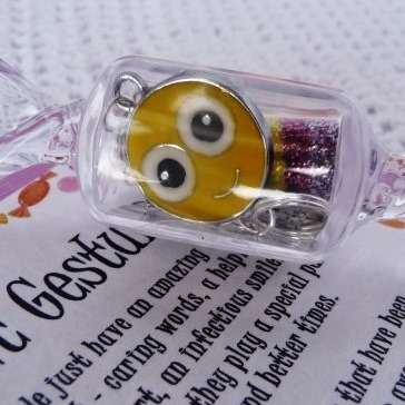 Cute smiley face charm in a candy shaped container begging to be opened!