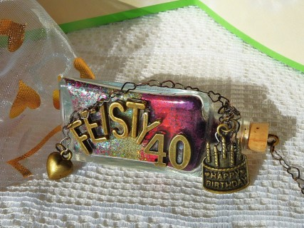 Feisty 40 wish bottle on its side with birthday cake charm