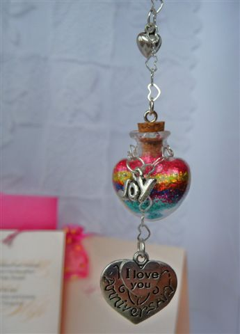 Closeup of hanging heartshaped mini wishing bottle says happy anniversary charm and wish layers