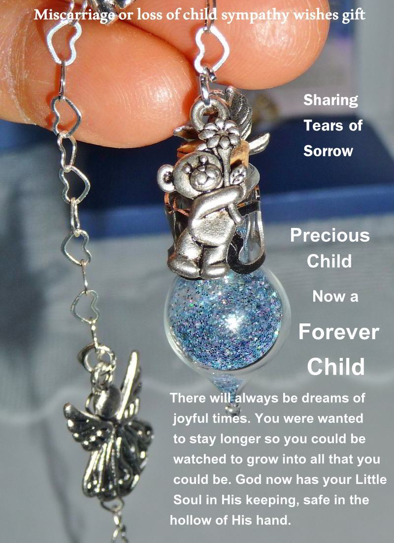 Extreme closeup of miniature tear wish vessel hanging from fingers with angel and teddy bear charms with a verse
