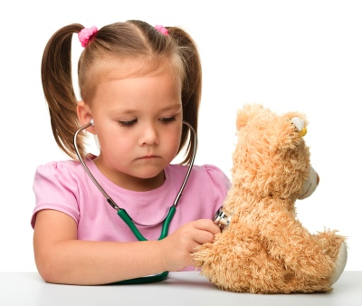 little girl with pigtails using a stethoscope on a teddy bear